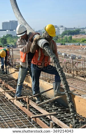 SELANGOR, MALAYSIA â?? MAY 2014: Construction workers are doing the concrete work using hose from the elephant crane or concrete pump crane on May 15, 2014 at Sepang, Malaysia.