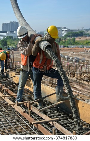 SELANGOR, MALAYSIA - MAY 2014: Construction workers are doing the concrete work using hose from the concrete pump crane on May 15, 2014 at Sepang, Malaysia.
