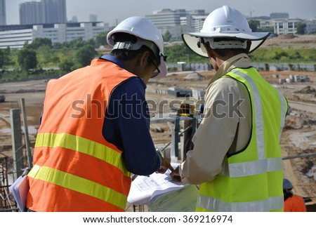 SELANGOR, MALAYSIA â?? MAY 15, 2014: Construction workers referring to the construction drawing plans at the construction site at Selangor, Malaysia.