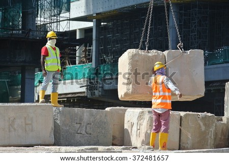 SELANGOR, MALAYSIA   MAY 25, 2015: Construction workers stacking the maintain load test block at the construction site in Selangor, Malaysia. The block used to test the piling integrity.