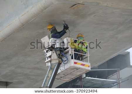 SELANGOR, MALAYSIA â?? MAY 26, 2015: Construction Workers standing in the mobile crane basket while working high level at the construction site in Malaysia.  - stock photo