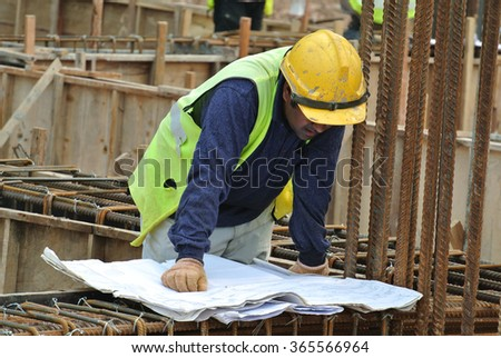 SELANGOR, MALAYSIA â?? OCTOBER 21, 2015: Construction workers referring to the construction drawing plans at the construction site at Selangor, Malaysia on October