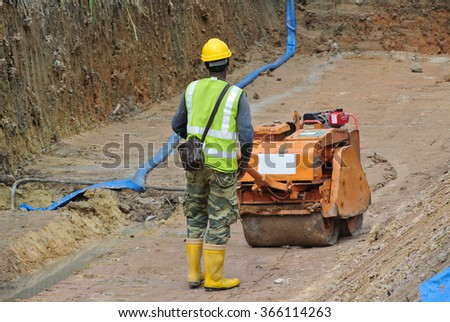 SELANGOR, MALAYSIA â?? SEPTEMBER 25, 2015: Construction workers using baby roller compactor to compact soil at the construction site in Selangor, Malaysia
