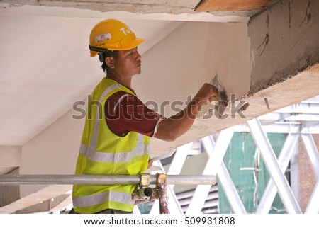 SELANGOR, MALAYSIA -SEPTEMBER 03, 2016: Site workers are doing soffit skim coat work at the construction site.
