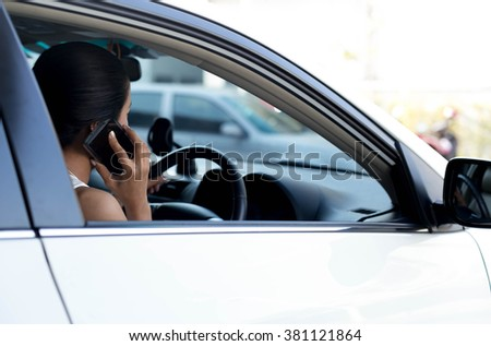 Selected focus cell phone Woman using cell phone while driving car - stock photo
