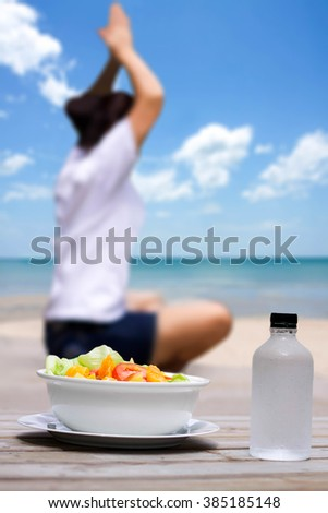 Selected focus fresh fruit salad with Woman relaxing Yoga on the beach as background