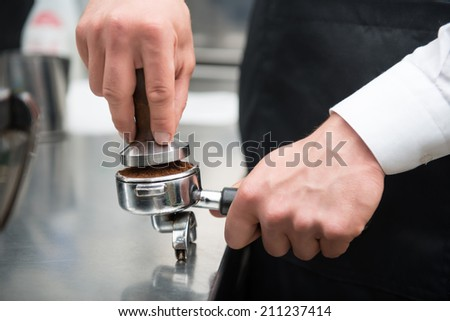 Selected focus on the hands of professional barista pressing coffee using the pounder with wooden handle. Coffee machine on background - stock photo