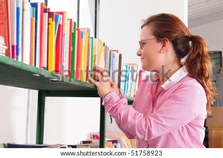 Selecting a book. - stock photo