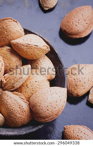 Selection of almonds in the vintage copper chinese bowl, black background - stock photo