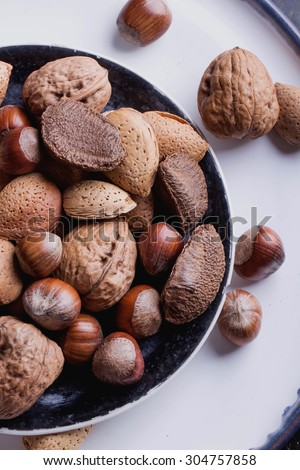 Selection of almonds in the vitage ceramic plate, black background, top view - stock photo