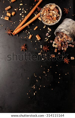 Selection of aromatic spices and sugar for hot winter beverages including cinnamon and star anise displayed on a dark background, overhead view with copyspace - stock photo