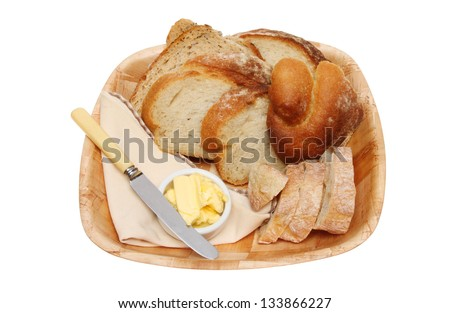 Selection of bread with a knife and butter and a serviette in a wooden bowl isolated against white