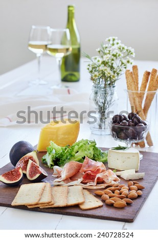 Selection of cheese and charcuterie with wine served as party snacks starters canapes - stock photo