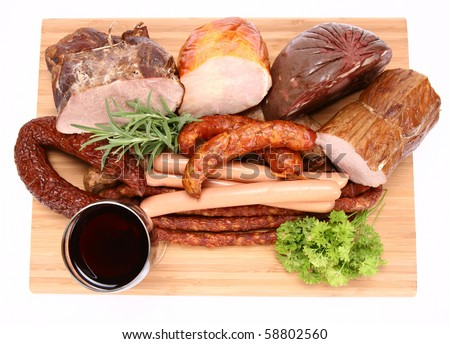 Selection of cold meat (ham, sirloin, headcheese, sausages, hot dogs) decorated with rosemary and parsley and a glass of red wine on a chopping board
