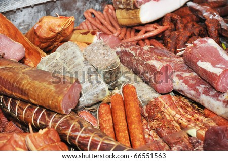 Selection of cold meat (ham smoked, sirloin, headcheese, sausages, hot dogs) at outdoor market - stock photo