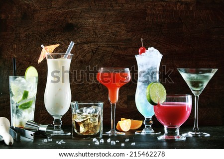 Selection of colorful festive Christmas drinks, alcoholic beverages and cocktails in elegant glasses on a dark background with copyspace - stock photo