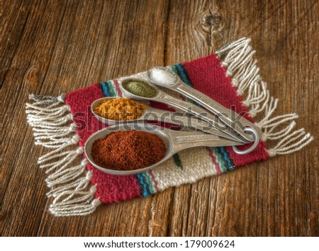 Selection of colorful spices in measuring spoons on an old worn wooden crate. - stock photo