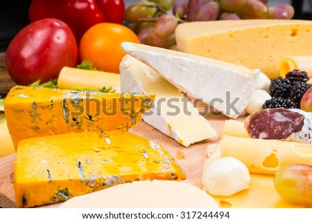 Selection of different cheeses on a platter with fresh salad ingredients and a bunch of grapes behind ready to be prepared and arranged on a buffet table - stock photo