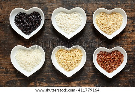 Selection of different rice grains in heart shaped dishes with par-boiled and husked white rice and long grain wild rice, overhead view on rustic wood - stock photo