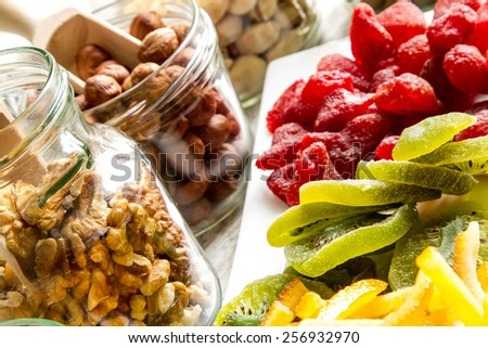 Selection of dried fruits in jars and on a plate  - stock photo