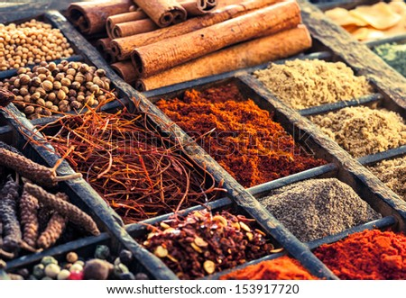 Selection of dried spices including peppercorns, red pepper, saffron and cinnamon in an old wooden printers tray, close up view - stock photo