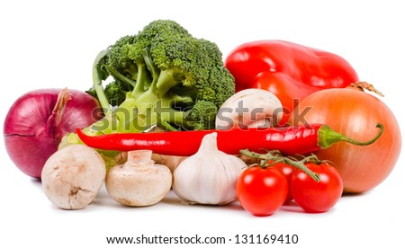 Selection of fresh colourful vegetables including, peppers, tomato, chilli, onions, mushrooms and broccoli on a white studio background - stock photo