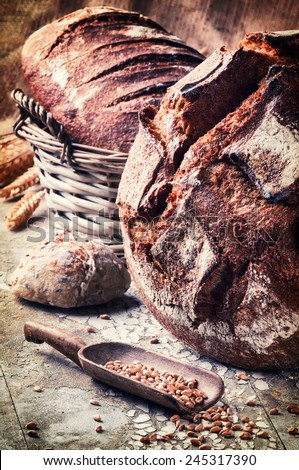 Selection of freshly baked bread in rustic setting  - stock photo