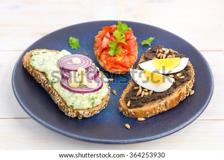 selection of Italian tomato Bruschetta with chopped tomatoes, herbs, black olive spread, hard boiled egg, soft cheese, red onion and oil grilled or toasted crusty multi grain bread rustic blue plate