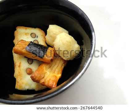 Selection of Japanese rice crackers in a black bowl with white space  - stock photo