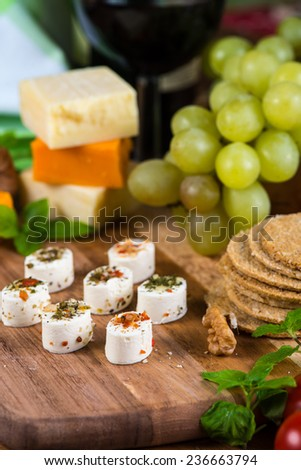Selection of party cheese snacks with herbs on board