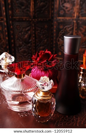 Selection of perfume bottles in romantic setting. Copy space on top. - stock photo