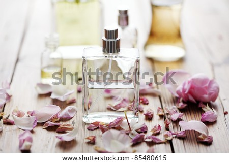 selection of perfume bottles surrounded by flower petals - stock photo