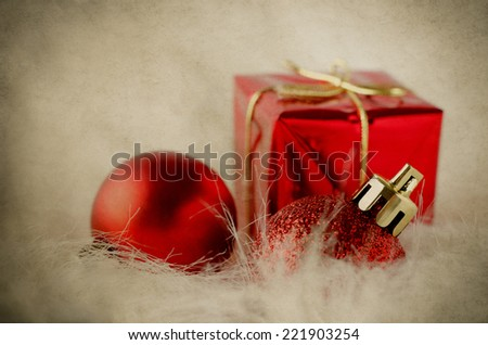 Selection of red and gold Christmas ornaments on white fake fur with yellowed and weathered vintage parchment effect. - stock photo