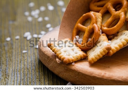 Selection of salty snacks, wood background, closeup