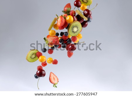 Selection of sliced and diced fruit, strawberries, kiwi, berries and cherries falling through the air. Image for a restaurant dessert menu or fruit salad for dieting, healthy food or fruit smoothies.