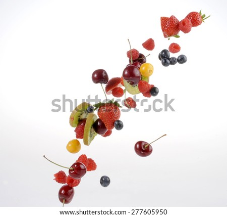 Selection of sliced and diced fruit, strawberries, kiwi, berries and cherries falling through the air. Image for a restaurant dessert menu or fruit salad for dieting, healthy food or fruit smoothies. - stock photo