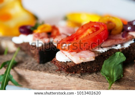 Selection of tasty Bruschetta: tomato and pepper grill, soft cheese, meat, Italian herbs, whole wheat bread.