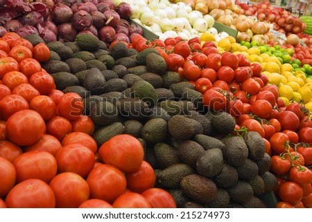Selection of tomatoes, avocados and red onions on display on market stall (full frame)