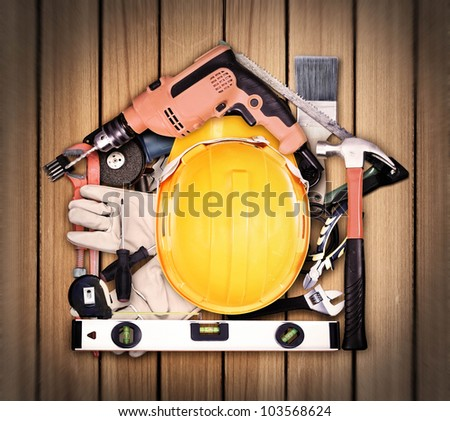 Selection of tools in the shape of a house, home improvement concept on old wood - stock photo