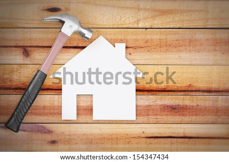 Selection of tools in the shape of a house on wood - stock photo