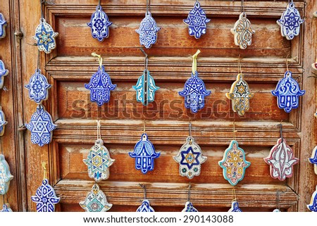 Selection of traditional Moroccan amulets, khamsa, providing defense against the evil eye, on a market in Fes - stock photo