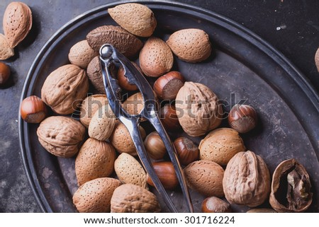 Selection of various nuts: almonds, Brazilian, walnuts on a vintage oval metal tray, black background, top view - stock photo