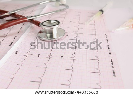 Selective focus A Stethoscope on the waveform from an ECG graph as a background and syringes. - stock photo