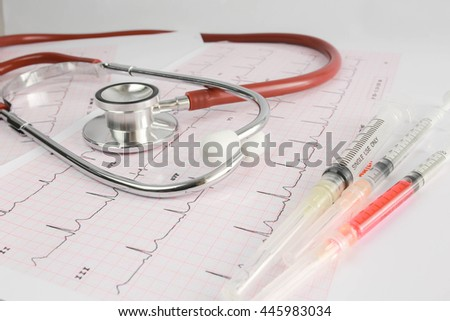 Selective focus A Stethoscope on the waveform from an ECG graph as a background and syringes in color tone. - stock photo