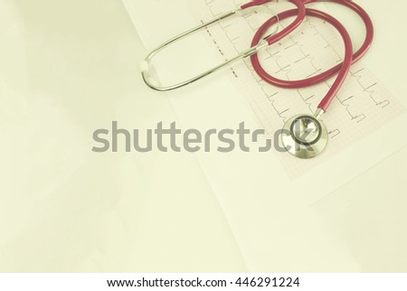 Selective focus A Stethoscope on the waveform from an ECG graph as a background  in color tone. - stock photo