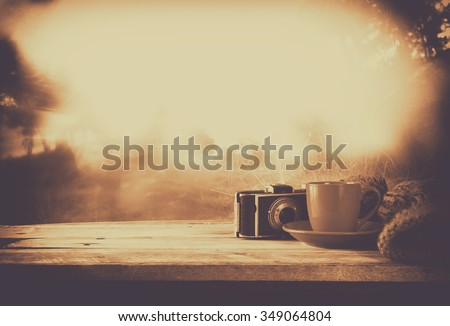 selective focus and abstract photo of cozy knitted hat with to cup of coffee next to old photo camera on a wooden table. faded style retro filtered and toned  - stock photo