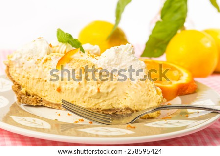 Selective focus and shallow depth of field on slice of Orange Chiffon Ice Box Pie garnished with orange zest and surrounded by colorful fruit and leaves. - stock photo