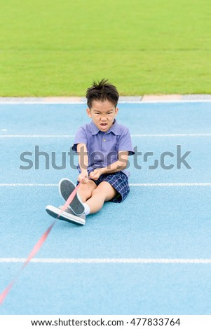 Selective focus at Young Asian boy pull a rope on blue track in the stadium.