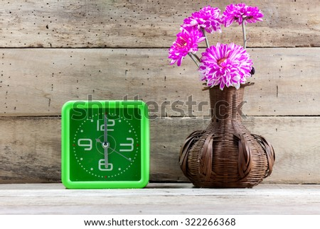 Selective focus beautiful pink flower in jar wood ,green clock on wooden background. - stock photo