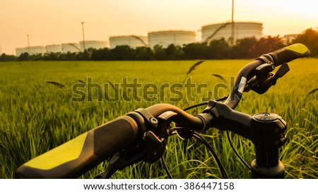 Selective focus :  bicycle stand round the grass field beside the oil warehouse at sunset